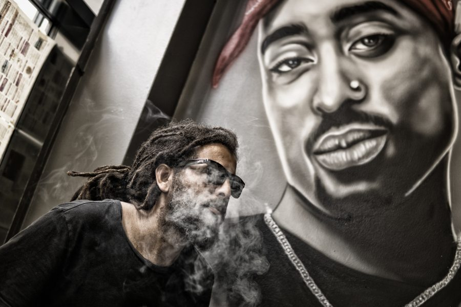 Man in front of 2Pac mural